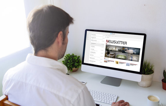 man reading newsletter on computer