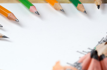 Pencil sharpener shavings on the white paper. Back to school