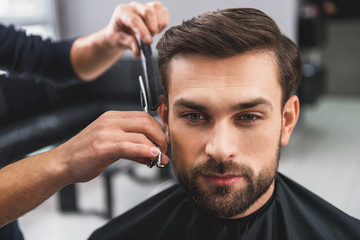 Skillful hairdresser cutting male hair