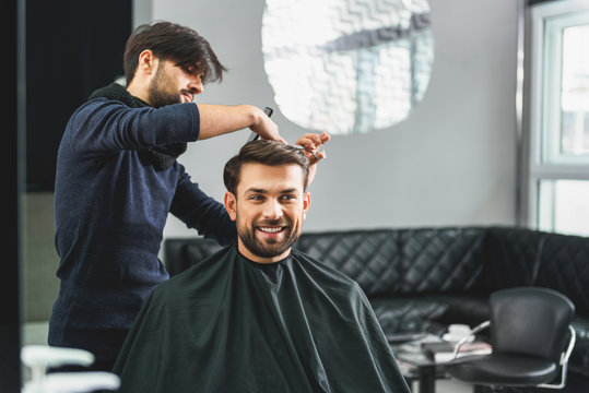 Happy guy getting haircut by hairdresser