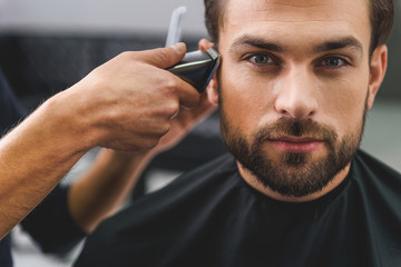 Confident guy sitting at beauty salon Wall mural
