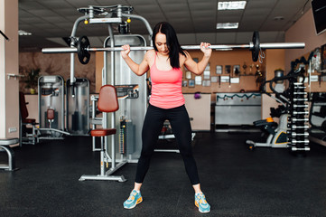 Beautiful fitness woman lifting barbell.