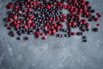 Frozen raspberry, blueberry, cranberry on grunge background. Frozen fruit. Flat lay, top view