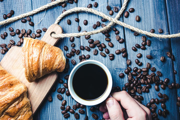 Hand holding white coffee cup on blue wooden table with croissant on borwn desk.