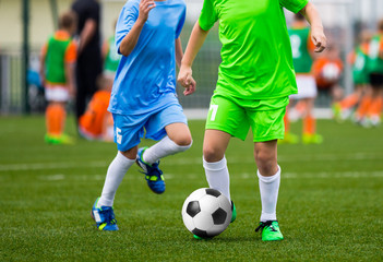 Youth Soccer Players. Boys Kicking Football Ball on the Field. Football Tournament for Kids. Soccer Pitch in the Background