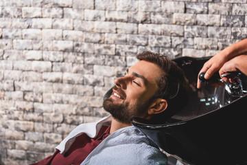 Joyful guy getting hairwash at barbershop