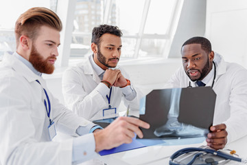 Confident three doctors analyzing x-ray photo