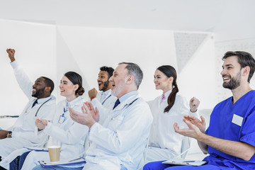 Happy doctors clapping hands on seminar