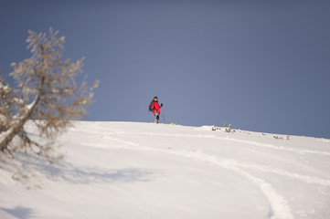 Man standing on top of the hill and preparing to go skiing down a piste. It is beautiful sunny day with blue sky.