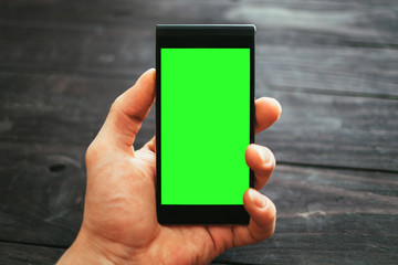 Male hand holding phone with green screen