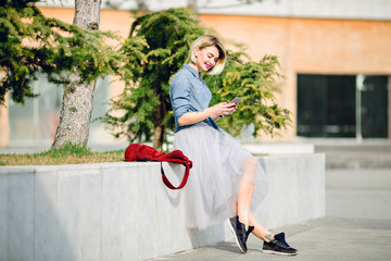 cute smiling blond girl with short hair and bright pink lips sitting in park and reading message on her smartphone wearing denim shirt, grey tulle skirt, black sneakers marsala backpack next to her