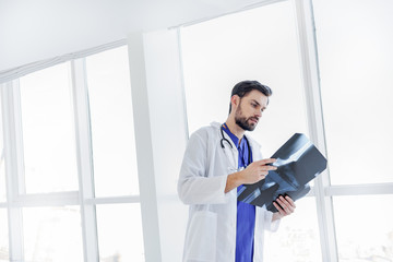 Serious young doctor analyzing radiograph