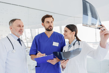 Professional medical team discussing roentgen picture
