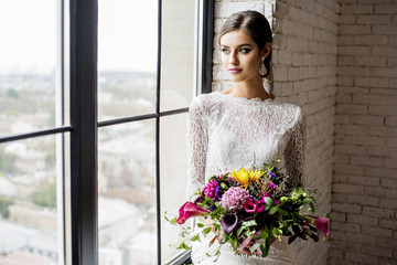 Modern bride in vintage dress with a wedding bouquet in hands