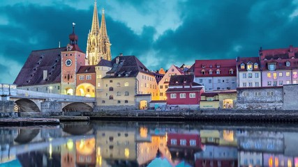 Fotomurales - Historical Stone Bridge, tower and buildings in the evening, Regensburg, Germany  (static image with animated sky and water)