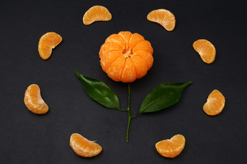 Fresh tangerines with leaves in the form of a flower on dark background