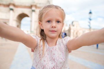 Adorable little girl taking selfie with mobile phone outdoors in Paris