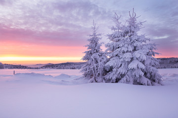 Sunrise over a cold winter landscape with beautiful illuminated clouds