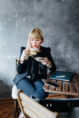 Business woman carefully sipping coffee while it cools down.