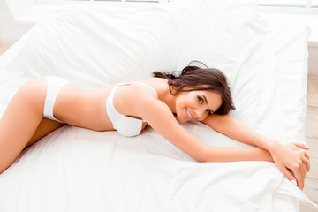 Pretty young smiling woman in lingerie lying on bed