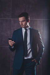 Young serious businessman  reading  message on mobile phone