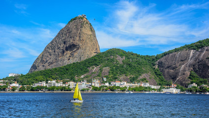 Yellow small sailing yacht and classic daytime scenic profile view of Sugarloaf Mountain, Pao de Acucar, standing above Botafogo Bay in Rio de Janeiro, Brazil