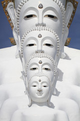 white buddha statue well alignment in front of blue sky and mountain in thailand