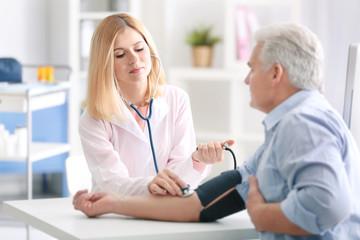 Doctor measuring blood pressure of patient