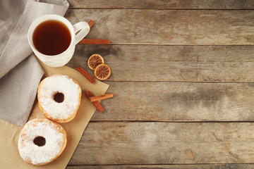 Delicious homemade doughnuts with sugar powder and cup of tea on wooden table
