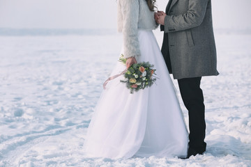 Happy wedding couple outdoors on winter day