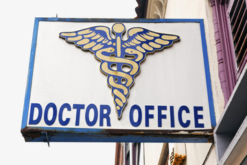 Doctor Office  with emblem sign attached to side of building