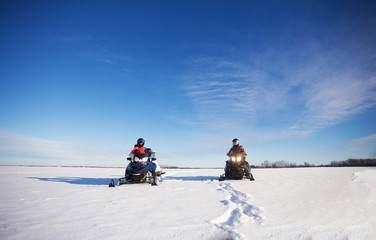A man and hid teenage daughter wearing helmets and winter gear parked side by side on their snowmobiles in a white winter landscape