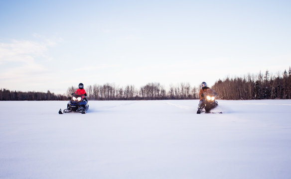 A father and his teenage daughter wearing helmets and winter gear racing side by side on snowmobiles across a white snow covered field with forest of trees in the background in a winter landscape