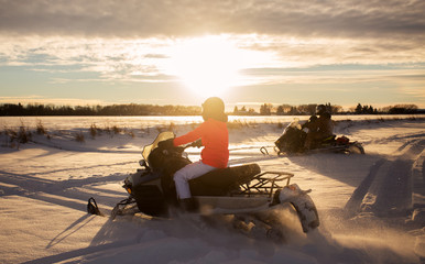 A father and his two gaughters riding two snowmobiles at sunset across a snow covered field in a winter landscape