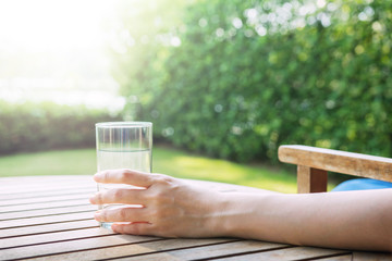 Female holding glass of water to drink at Backyard
