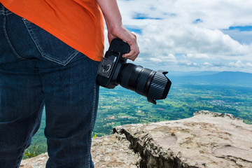 Woman with digital camera at view point on mountain. Travel life