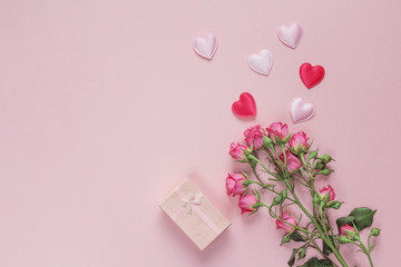 Bouquet of roses, gift box and hearts on a pink background. Spac