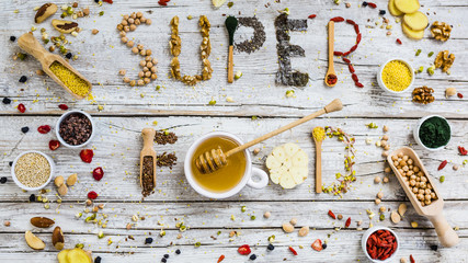 Superfoods and healthy food on wooden background.
