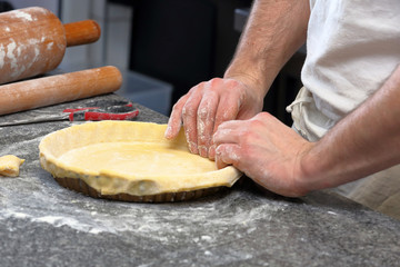 Baker kneading dough for tart in a bakery