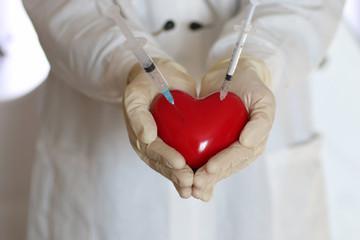 syringe in heart doctor hand