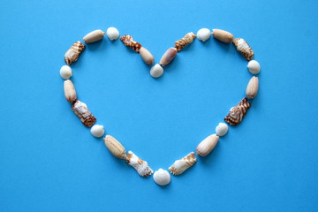 A heart from different seashells on the blue background for Valentine's Day.