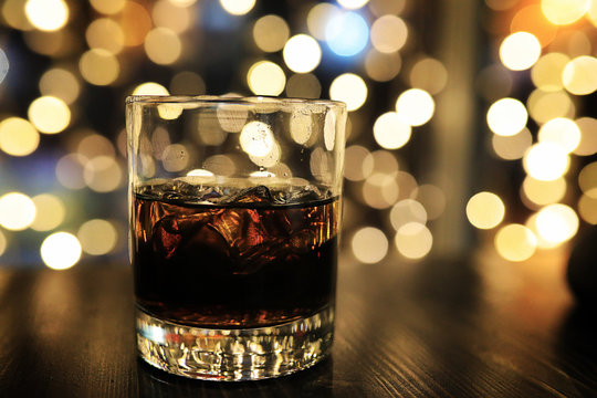 glass of alcohol with ice on blured background with circle bokeh