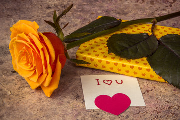 Orange rose, gift covered in hearted paper and note I love you