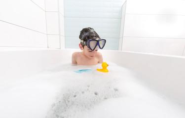 boy swims in the bathtub