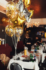 Golden and silver balloons in form of stars hang over dinner tab