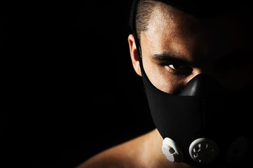 Portrait of male athlete wearing training mask. Wall mural