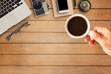 Hand holding coffee cup with office equipment