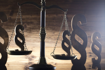 Law and justice concept. Scales of justice, gavel, paragraphs, brown wooden background, place for text