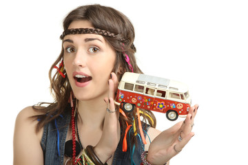 Happy hippie girl holding a toy bus isolated on white background.