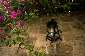 Lantern and pink flowers on the street, Rhodes, Greece.